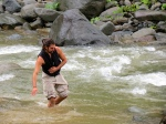 Caelan wading in a river in Costa Rica